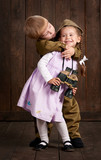 children boy are dressed as soldier in retro military uniforms and girl in pink dress - 209844010