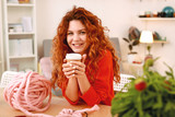 Take away coffee. Smiling red-haired skillful art student drinking tasty take away coffee at the art class