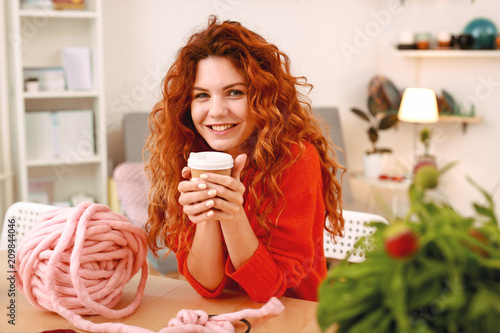 Wall mural Take away coffee. Smiling red-haired skillful art student drinking tasty take away coffee at the art class