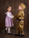 children boy are dressed as soldier in retro military uniforms and girl in pink dress - 209844205
