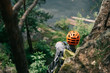 rear view of male hiker in protective helmet standing on rocky cliff in forest