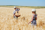 child boy and girl with guitar are in the yellow wheat field, bright sun, summer landscape - 209844834