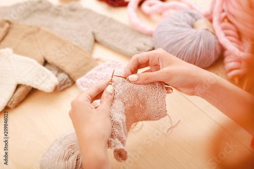 Inspirowana szwaczka. Inspirowana zmotywowana szykownica czuje się niesamowicie zadziwiająco podczas robienia małego beżowego swetra dla córki