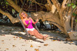 Gorgeous blond woman is rocking under the tree