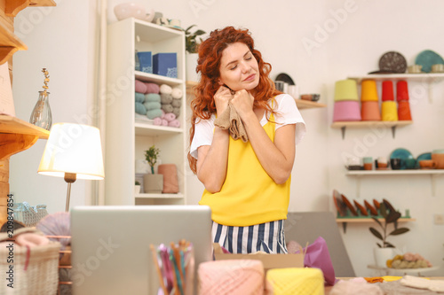 Foto Murales Work in studio. Amicable young red-haired woman wearing stylish bright yellow shirt working in spacious light art studio