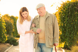 Senior man with cane and nurse from care home walking in park - 209848205