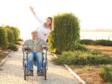 Nurse from care home and senior man in wheelchair walking outdoors - 209848216
