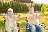Senior man and woman from care home doing exercise outdoors - 209848225