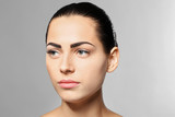 Young woman with permanent eyebrows makeup on grey background - 209848664