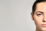 Young woman with permanent eyebrows makeup on grey background - 209848676
