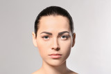 Young woman with permanent eyebrows makeup on grey background - 209848686