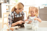 Mother with daughter making dough together in kitchen - 209848845