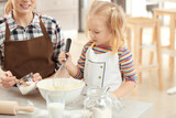 Mother with daughter making dough together in kitchen - 209848848
