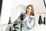 Young female photographer working in studio - 209849055