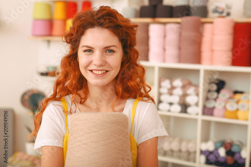 Foto Murales Bright idea. Beaming creative red-haired girl having a very bright idea of knitting oversize bright sweater for winter