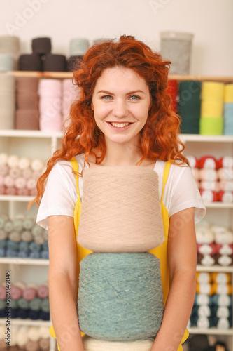 Kolorowe clews. Rudowłosa promienna dziewczyna czuje się wyjątkowo entuzjastycznie, trzymając trzy duże kolorowe nożyczki