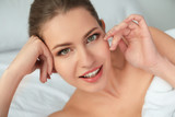 Young woman applying cream onto her skin, closeup - 209849425