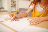 Drawing picture. Woman wearing bright yellow shirt enjoying her weekend at home while drawing nice picture
