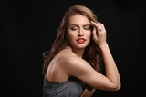 Beautiful young woman with elegant jewelry on dark background - 209849481