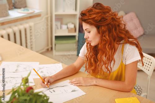 Foto Murales White and yellow. Beautiful inspired woman wearing stylish fashionable white and yellow shirt drawing portrait
