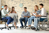 Young man in wheelchair with colleagues at workplace - 209849822