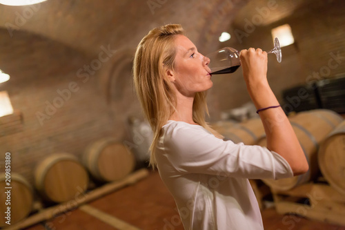 Foto Murales Beautiful woman oenologist tasting wine