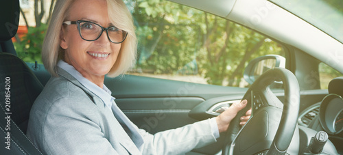 aged woman toothy smiling while driving a car