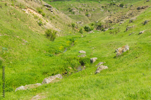 Fotobehang Pistache A picturesque panoramic view on green hills with rocks on a summer day in Saharna, Moldova