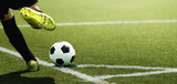 Foot of a child football player and ball on the football field, kicking a corner kick - 209859809