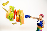 A young woman beats his fist a chicken burger. The concept is the fight against unhealthy food. - 209867486
