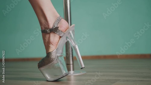 Young woman on high heels walks around a pole close up.