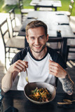 high angle view of smiling man looking at camera while eating asian food in cafe - 209868688
