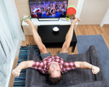 a excitement man gesturing hands with legs up when watching soccer in television at home, from above view. Happy man watching sport in TV. Football fan celebrates goal.