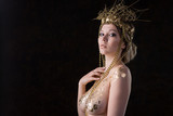 Young woman in a gold dress and crown - 209874863