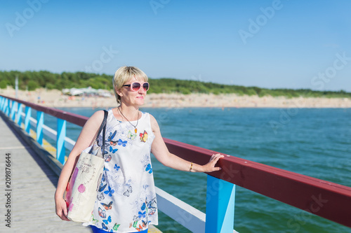 Foto Murales The beautiful adult woman in sun-protection glasses stand in bridge