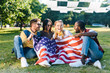 multiracial happy friends with american flag sitting on green grass in park