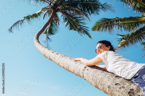 Aluminium Bali Woman lies on the palm tree. Summer vacation concept image
