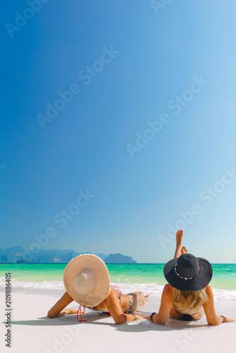 women sunbathing lying down on the tropical beach - 209886405