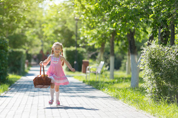 The girl runs along the road with a basket of bread. A little girl runs along the street in the city with bread and baking.