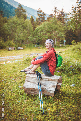 Woman hiker sitting on the log in forest. Tourism concept - 209891658