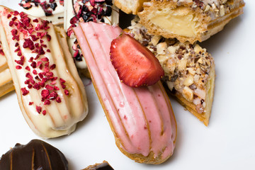 Sweet and colorful french eclairs with berrys, chocolate, nuts. Group of french dessert. Eclair background. Delicious colorful eclair.
