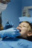 Dentists with a patient during a dental intervention to boy.
