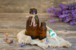 Lavender oil in different bottles on wooden background.