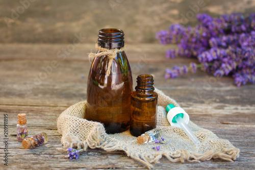 Lavender oil in different bottles on wooden background. - 209911895