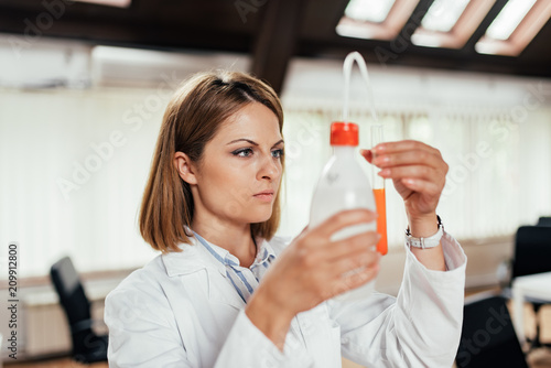 Foto Murales Scientific researcher holding a water in plastic bottles with a pump. Close-up.