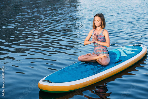 Aluminium School de yoga Young woman meditating on paddle board. practice yoga on paddle board, woman sitting on paddle board, yoga on sup board at sea
