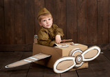 children boy are dressed as soldier in retro military uniforms sit in an airplane made of cardboard box and dreams of becoming a pilot, dark wood background, retro style - 209915029