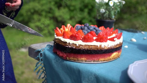 Slicing beautiful cake with fruits