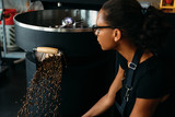 Young entrepreneur sitting at roasting machine, controlling a prepared roasting beans - 209921610