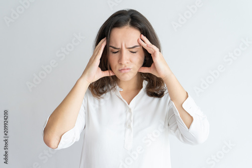 Leinwanddruck Bild Frustrated tired girl suffering from headache. Young Caucasian woman in white blouse touching head with pain grimace. Health care and head ache concept